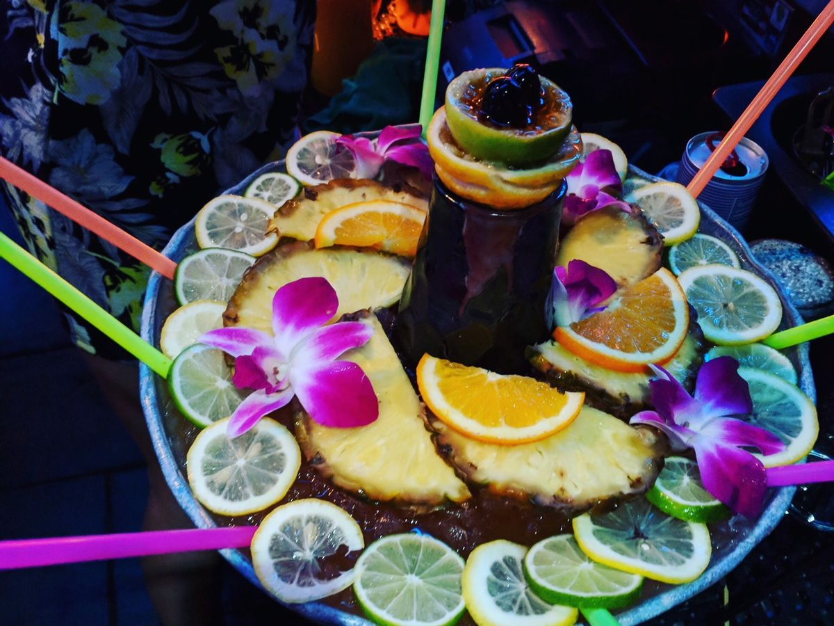 A big shareable cocktail is served in a giant bowl with lots of colorful straws, citrus slices, and orchids