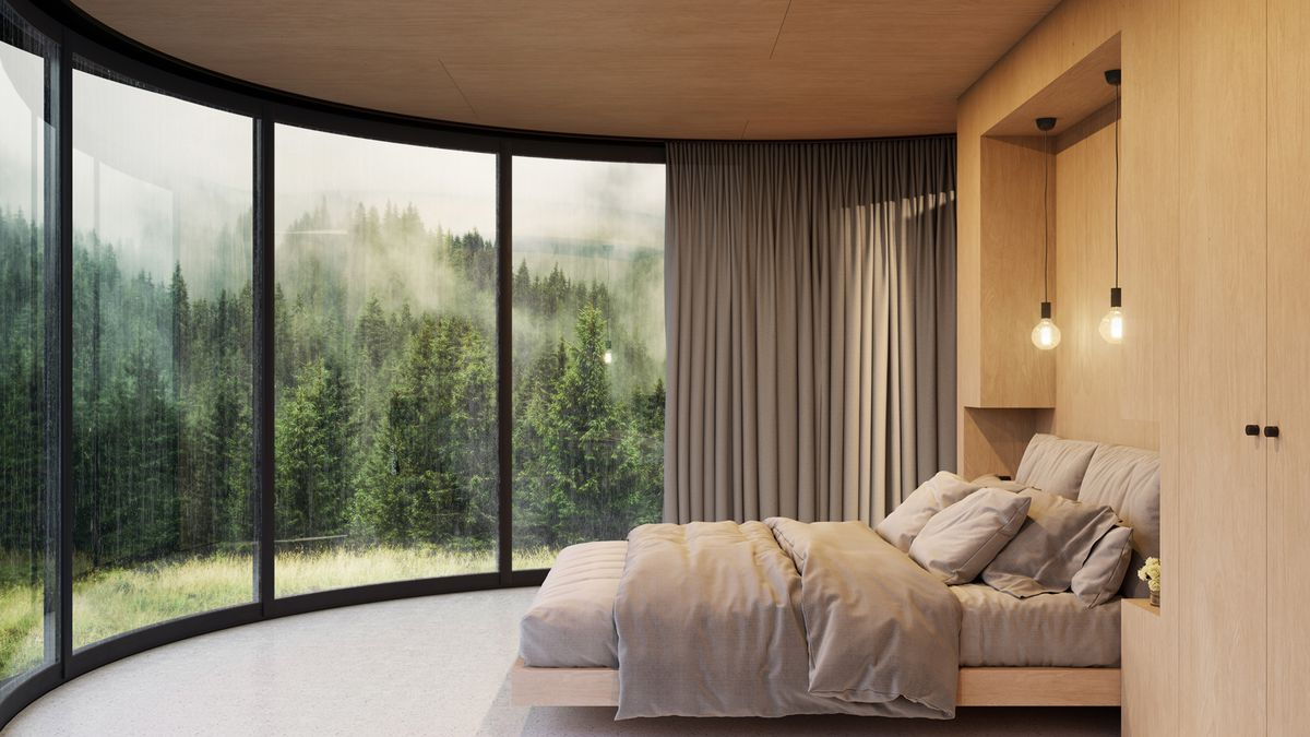 Bed in room with curved glass wall