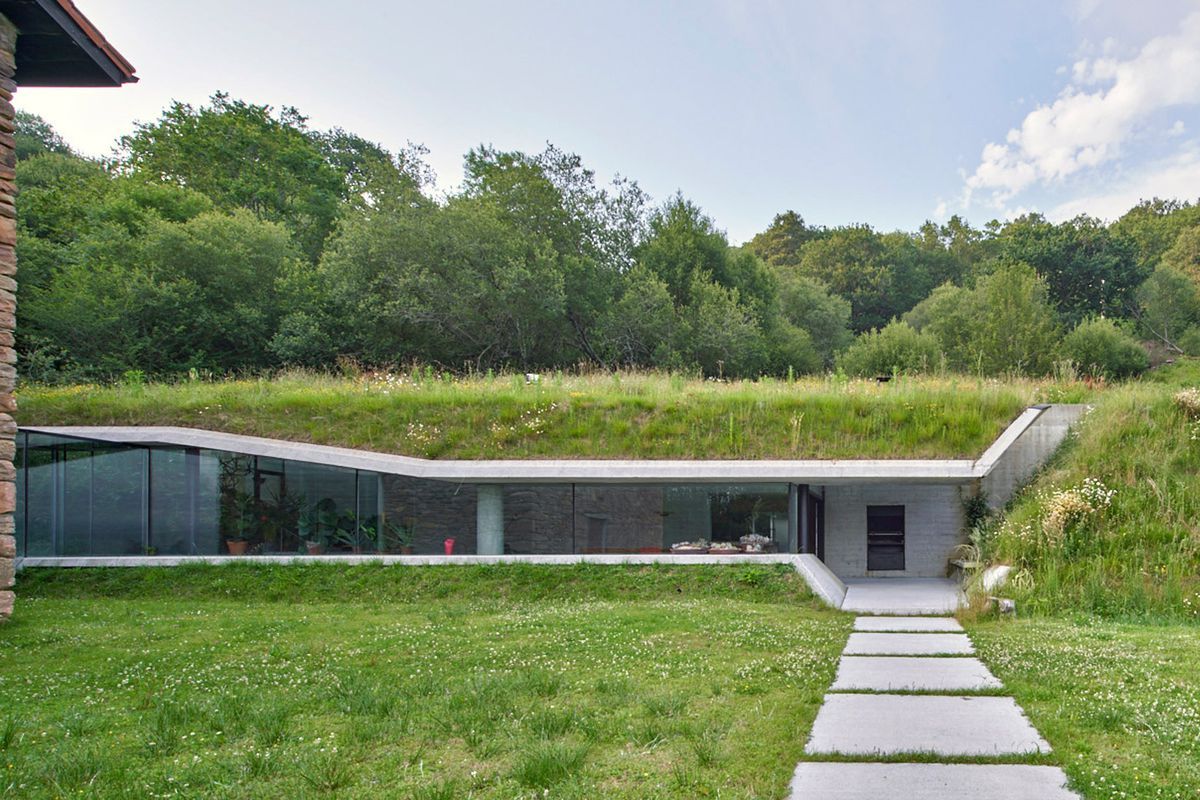 Concrete and glass structure built into side of hill.