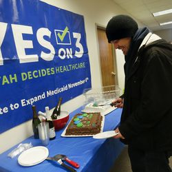 Wessly Berry, of Murray, cuts a cake after enrolling in a Medicaid plan during a Medicaid expansion celebration and enrollment event at the Utah Health Policy Project in West Valley City on Wednesday, Jan. 15, 2020.