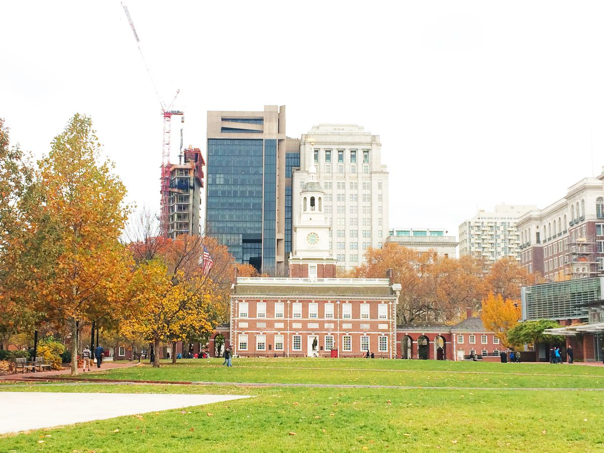 Independence Hall in Philadelphia. The building is surrounded by trees with colorful fall foliage.