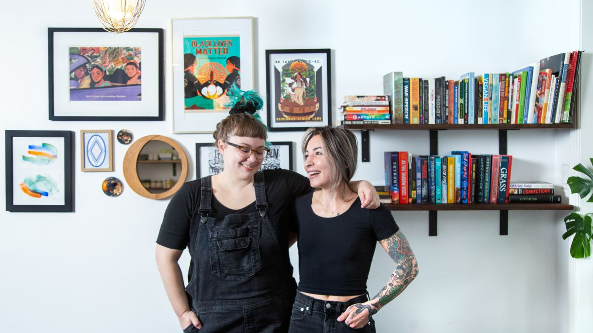 two women standing with one arm over the other in front of a bookshelf and a gallery wall of art