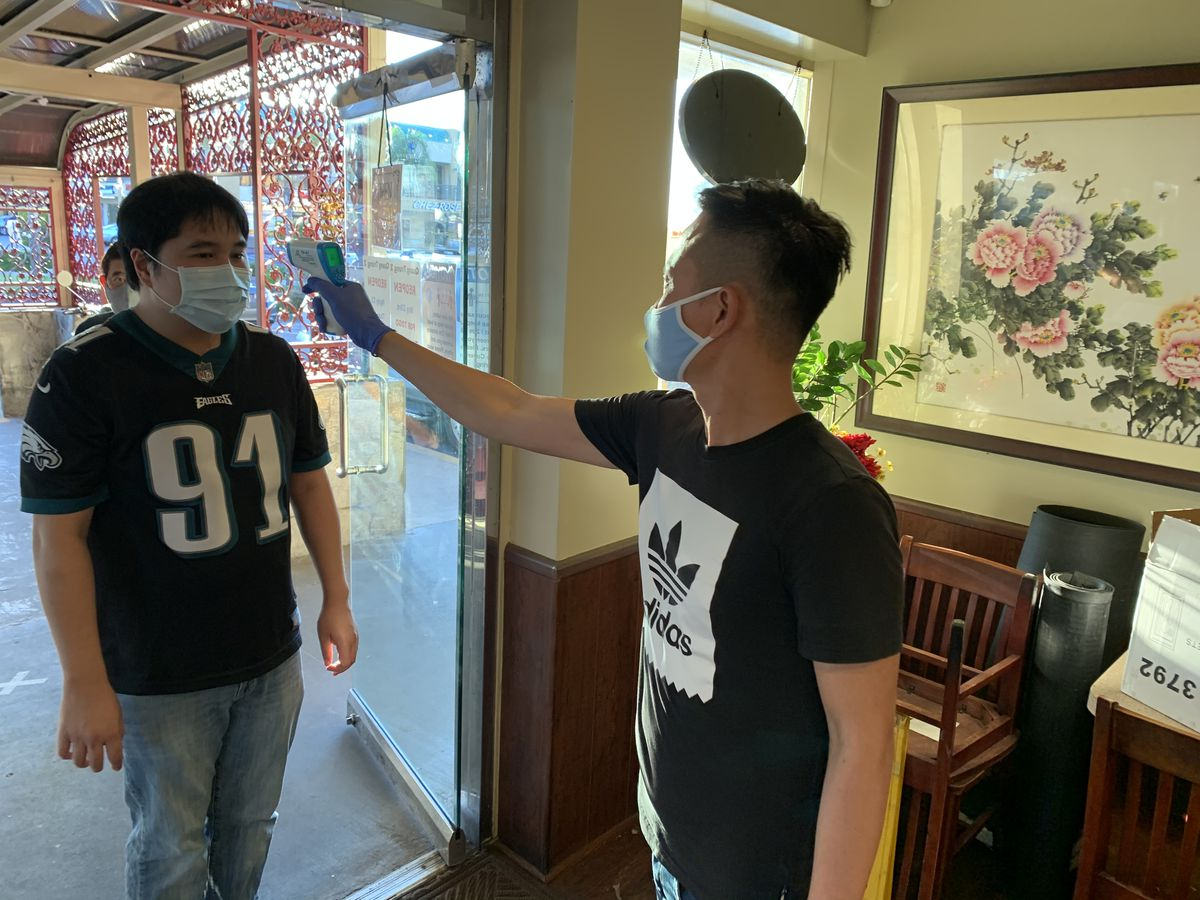 Staff checks temperature of a prospective diner at Pho Quan Trung in Westminster