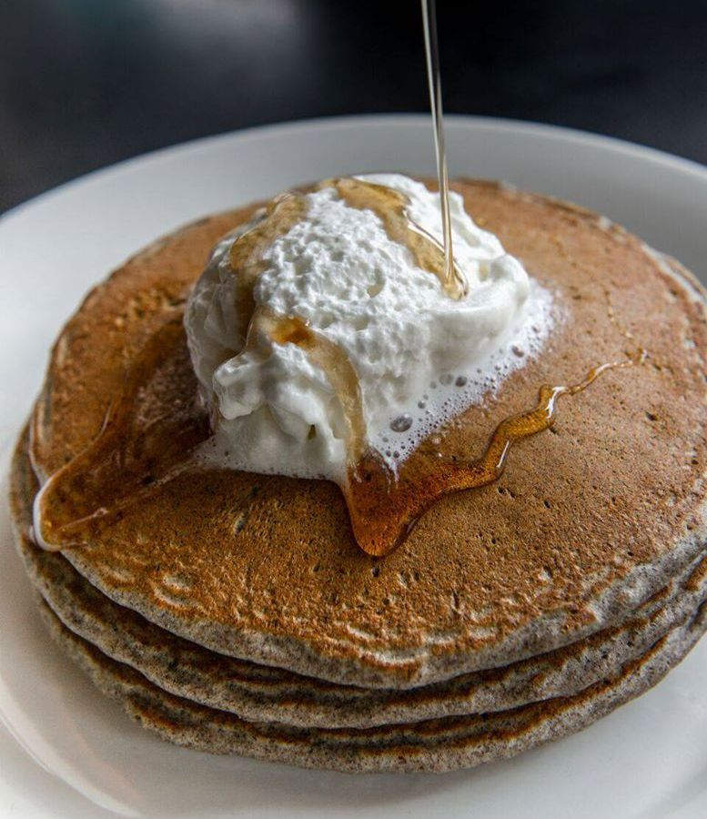 A stack of simple buttermilk pancakes with butter and syrup