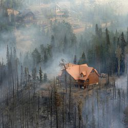 Smoke from the Brian Head Fire surrounds homes in the Brian Head area on Friday June 23, 2017. The fire continues to grow and has burned more than 27,700 acres. At least 13 homes and eight out buildings have been destroyed.