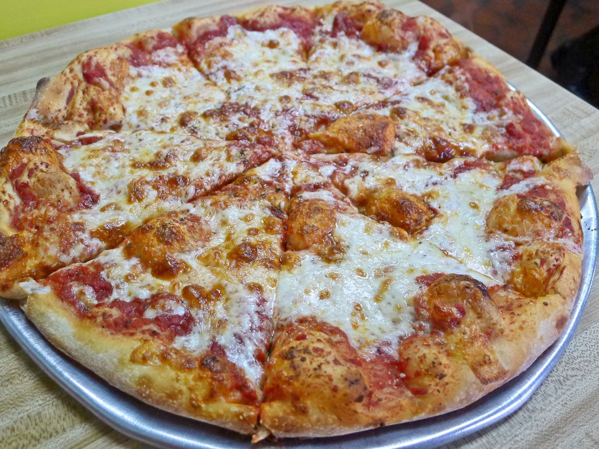 A whole pizza with irregularly applied cheese and meat, and a puffy crust.