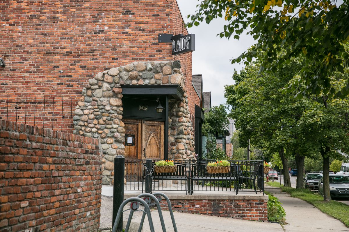 """Lady of the House's """"Lady"""" sign hangs over the corner entrance to its brick building decorated with big stones."""