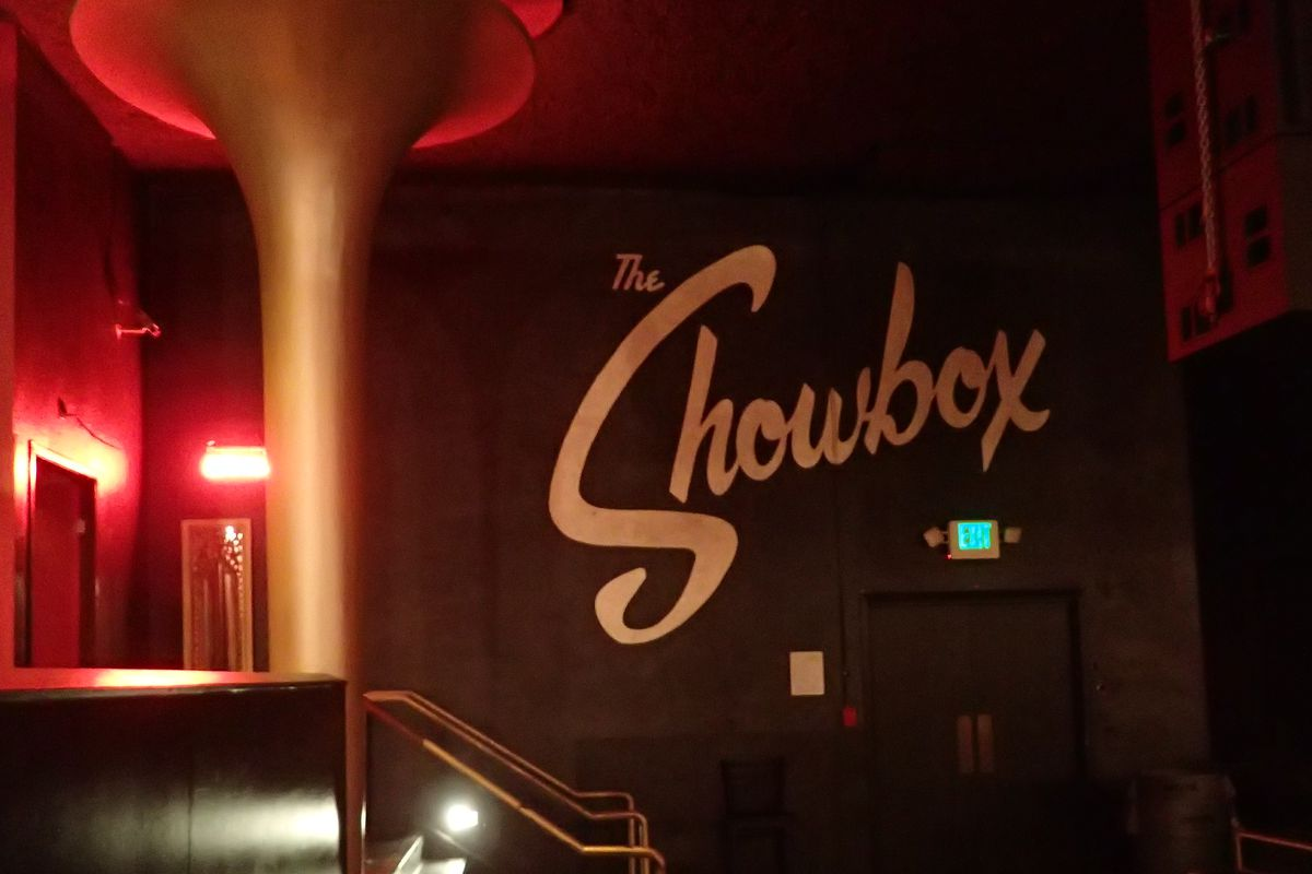 A photo shows the interior of the Showbox, including a column on the left and the venue's logo painted in white on a black wall.