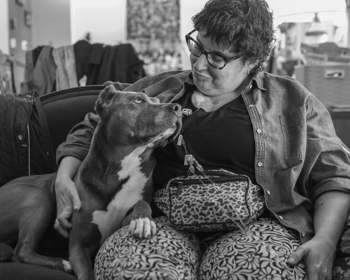 """Stacy Oliver and her beloved dog Lulu, who died this year. When illness made her unsteady on her feet, she fell, dropping the dog's leash. Instead of running off, """"Lulu spread her legs out like a table and let Stacy pull herself up,"""" her husband said."""
