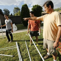 Ted Martinez instructs Latter-day Saint missionaries Elders Jacob Holden and Carter Sanders as they help Catholics set up for the Carmelite Fair at the monastery in Holladay Tuesday, Sept. 16, 2014.