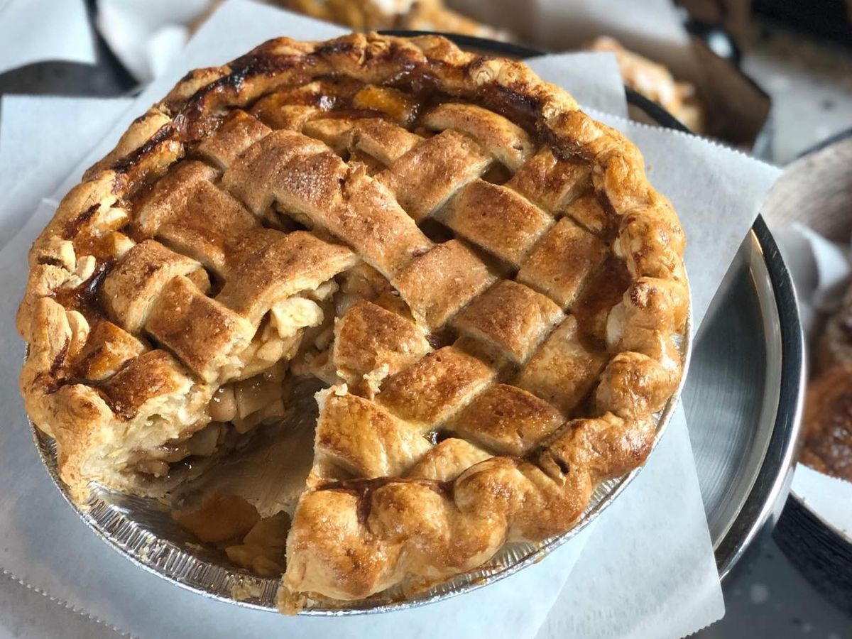 A large pie with a slice cut out shows layers and layers of spiced apples inside. The top of the pie has a lattice crust.