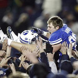 BYU tight end Andrew George (88)  is carried off the field after scoring the winning touchdown against Utah at LaVell Edwards Stadium in Provo Saturday. BYU won in overtime 26-23.