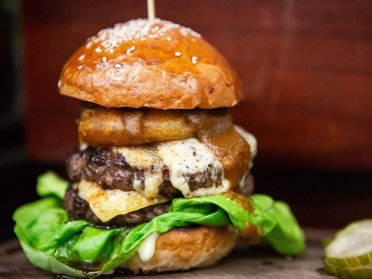A double decker burger with an onion ring from P.S. Steak