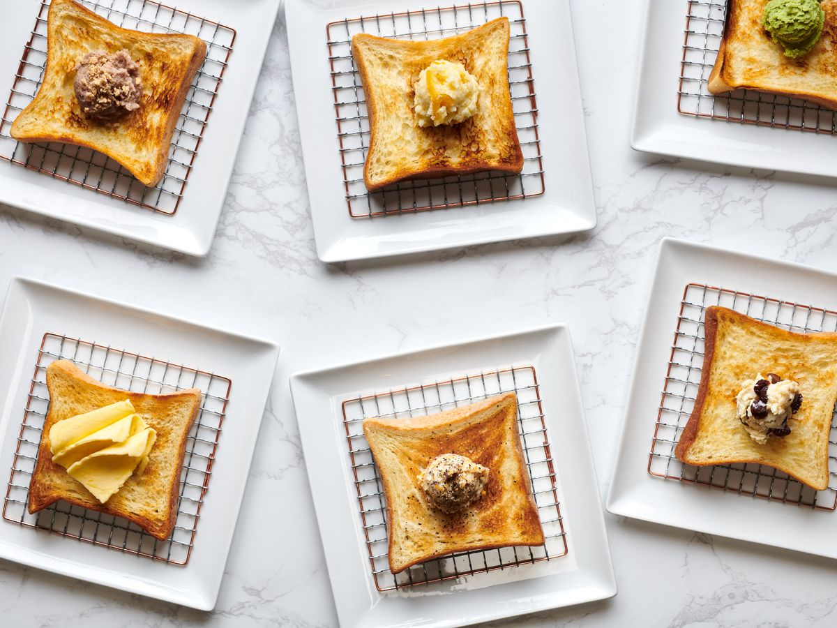 Six pieces of shokupan toast sit on a white marble counter under grates at Kimura Toast Bar