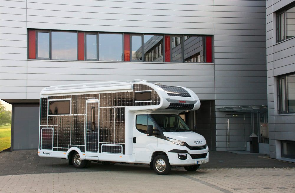 A white camper parked outside of a house. The camper has solar panels on the side of it.