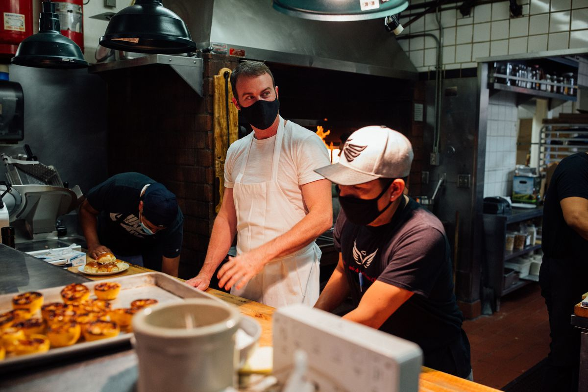 A chef in simple whites with a facemask cooks inside of a Southern restaurant at night.