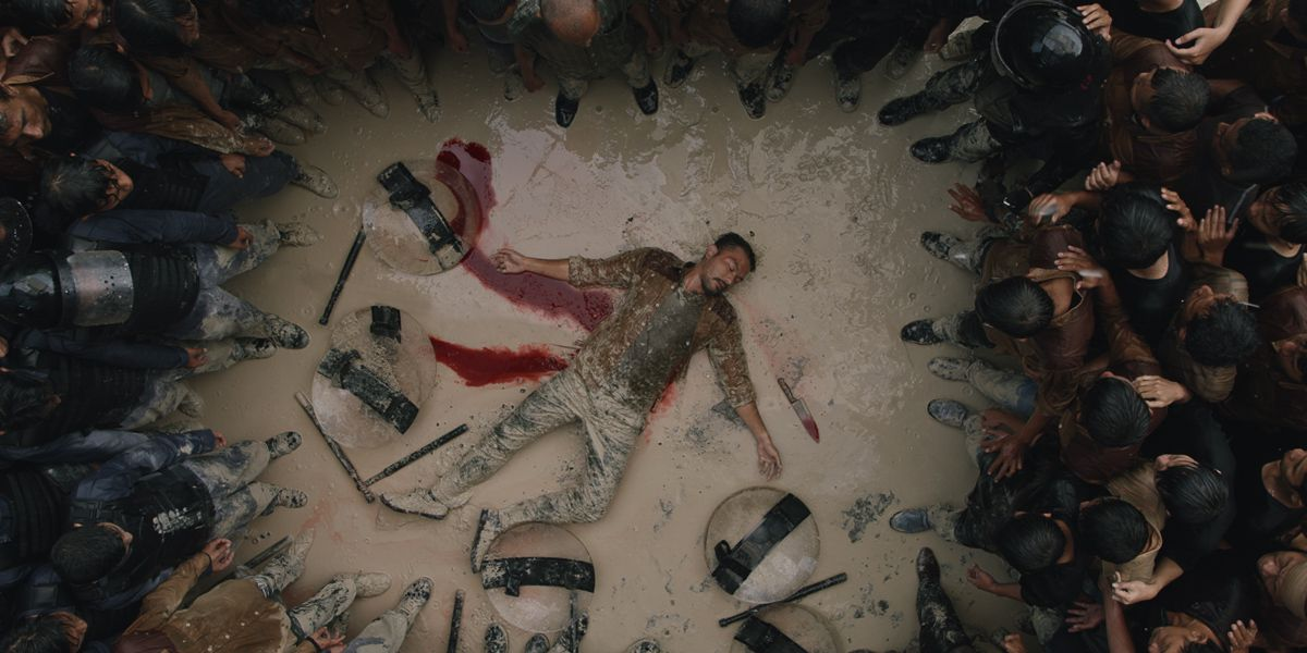 a man surrounded by a crowd of onlookers and a few fallen shields bleeds out onto the muddy ground