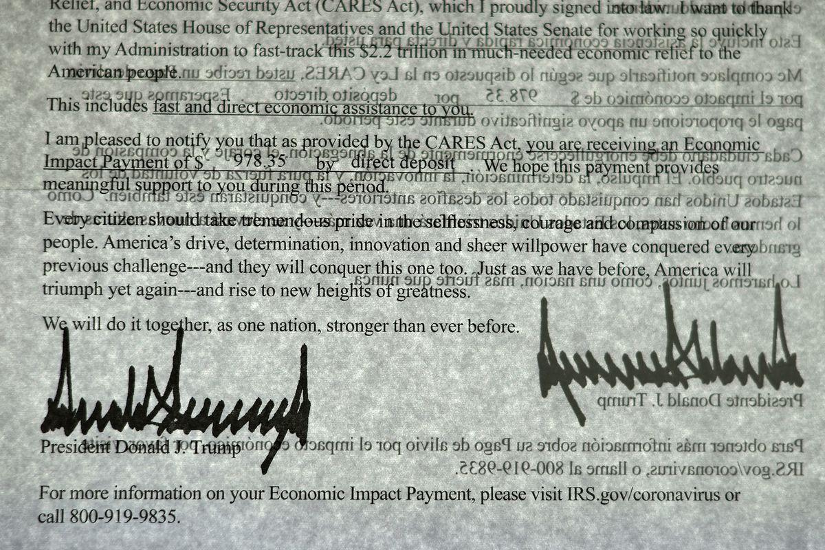 President Donald Trump's signature can be seen twice as light shines through a letter printed in both English and Spanish that was sent to people who received a coronavirus economic stimulus payment as part of the Cares Act on April 29 in Washington, DC.