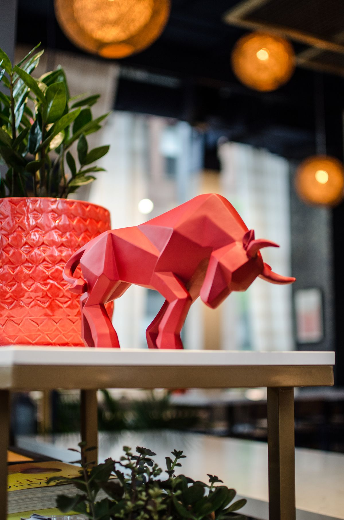 A bright red bull figurine sits next to a red flower pot holding a succulent on a small shelf. Another plant and books are visible in the corner, and the background shows a high-ceilinged restaurant with large spherical light fixtures.