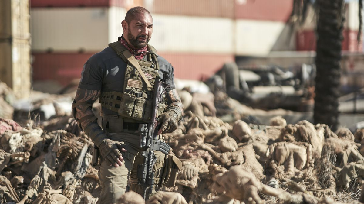 Dave Bautista stands in a field of dead, desiccated bodies in Army of the Dead