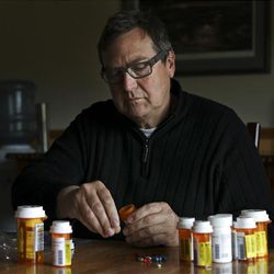 Tim Nelson sits at a table with medication that he has to take twice a day for his cancer during the Reel Recovery fly-fishing retreat at Falcon's Ledge lodge near Altamont.