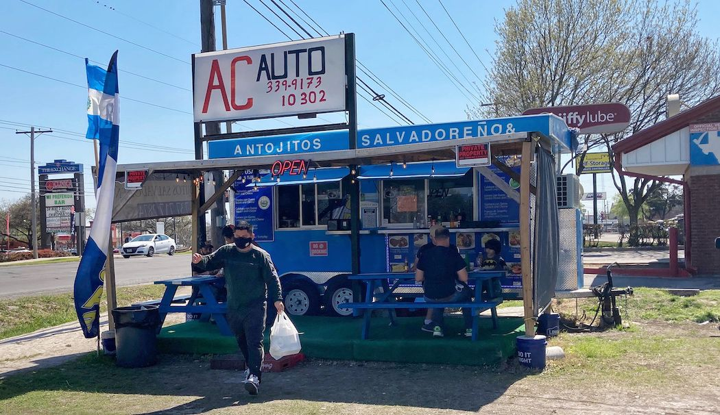 A sign for AC Auto hangs over a blue food truck selling antojitos.