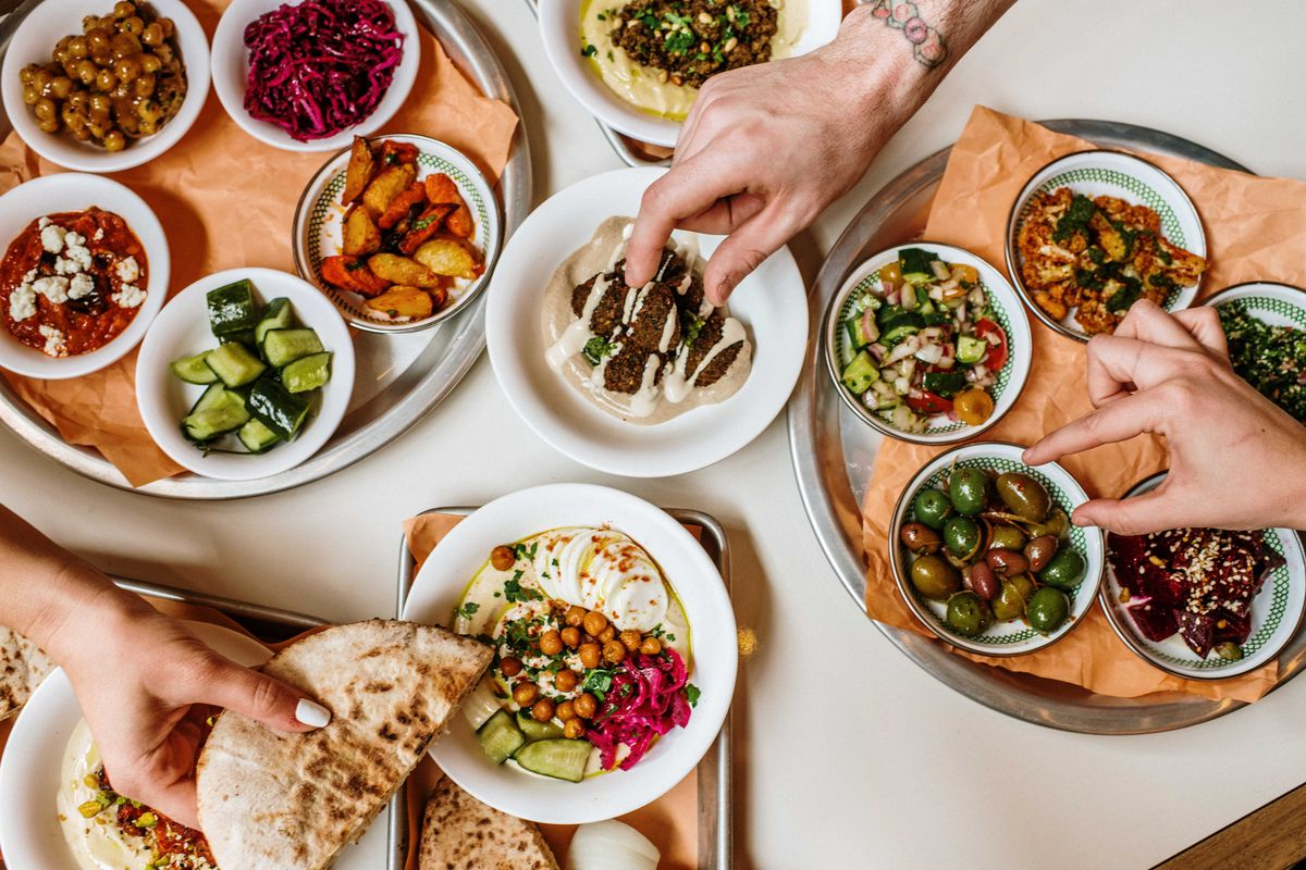 Three platters of mezze with olives, hummus, pita, chickpeas, pickled vegetables