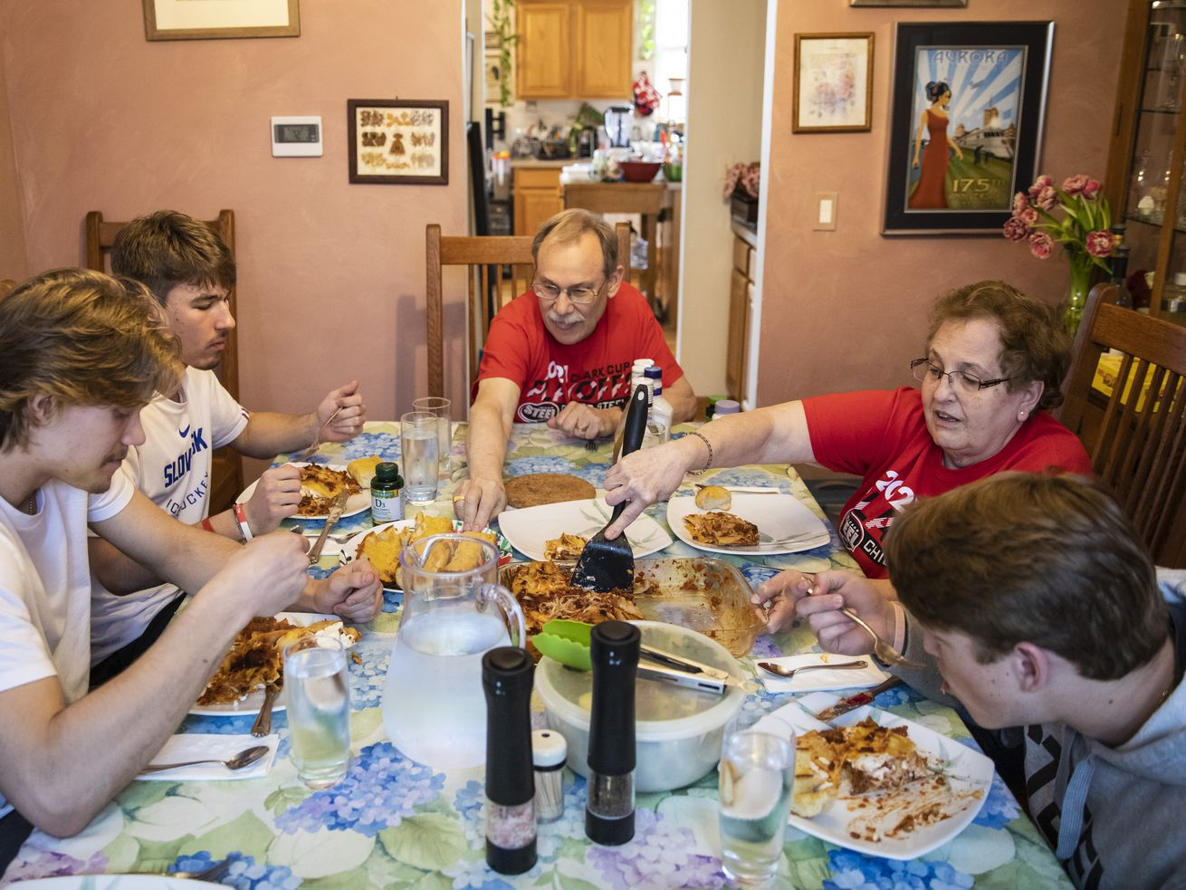 (From left) Jack Bar, Simon Latkoczy, Brian Gravenhorst, Marcy Gravenhorst and Lukas Gustafsson sit down for a lasagna dinner at the Gravenhorst home in Aurora, Wednesday evening, April 28, 2021. Brian and Marcie Gravenhorst are a billet family for Chicago Steel players Bar, Latkoczy and Gustafsson, who are from Canada, Slovakia and the American state of Georgia, respectively. | Ashlee Rezin Garcia/Sun-Times