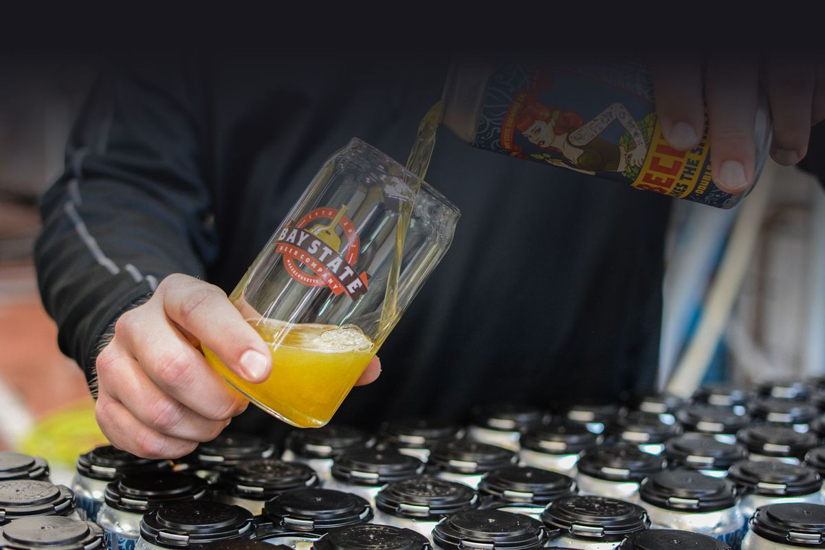 A hand pours beer from a can into a glass, both objects tilt toward each other