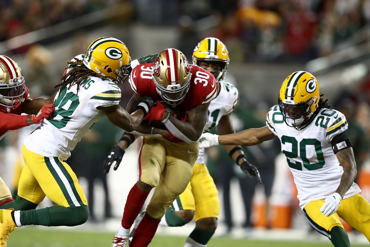 Jeff Wilson of the San Francisco 49ers is tackled by Tramon Williams and Kevin King of the Green Bay Packers at Levi's Stadium on November 24, 2019 in Santa Clara, California.
