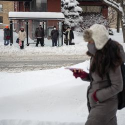 A pedestrian walks as commuters wait for a bus in the Edgewater neighborhood, Tuesday morning, Feb. 16, 2021, after a snowstorm dumped over a foot of snow in Chicago starting Sunday night. Snow is expected to continue to fall until Tuesday night.