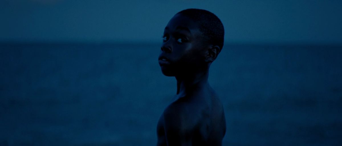 a young black boy looks over his shoulder while standing in front of the ocean in Moonlight (2016)