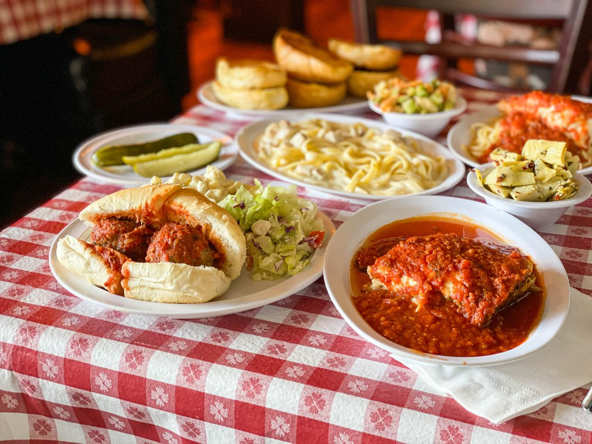 A red cloth table of meatballs, lasagna, and more.