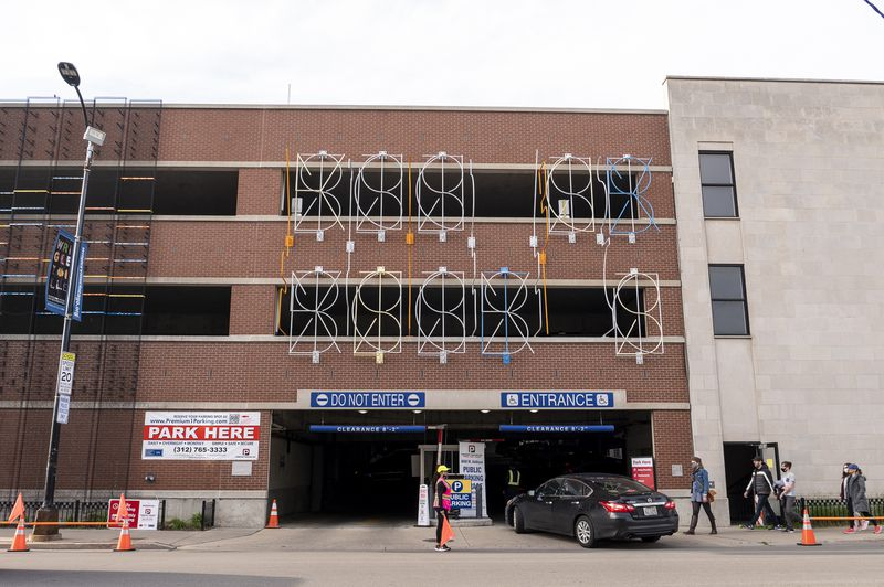 Parking attendants with Premium 1 Parking flag drivers during a Cubs home game Monday to park in a garage at 808 W. Addison St. that InterAmerican Elementary Magnet School shares and that it leases to the company.