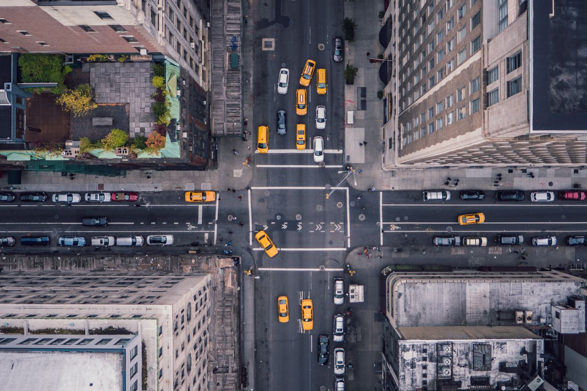 An overheard shot of New York City's 5th Avenue intersection, with yellow cabs driving by.
