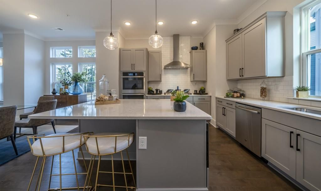 A large kitchen with a variety of windows and gray cabinetry.