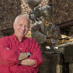 Portrait of artist James C Christensen posing with his fountain in the Shops at Riverwoods in Provo, Utah.