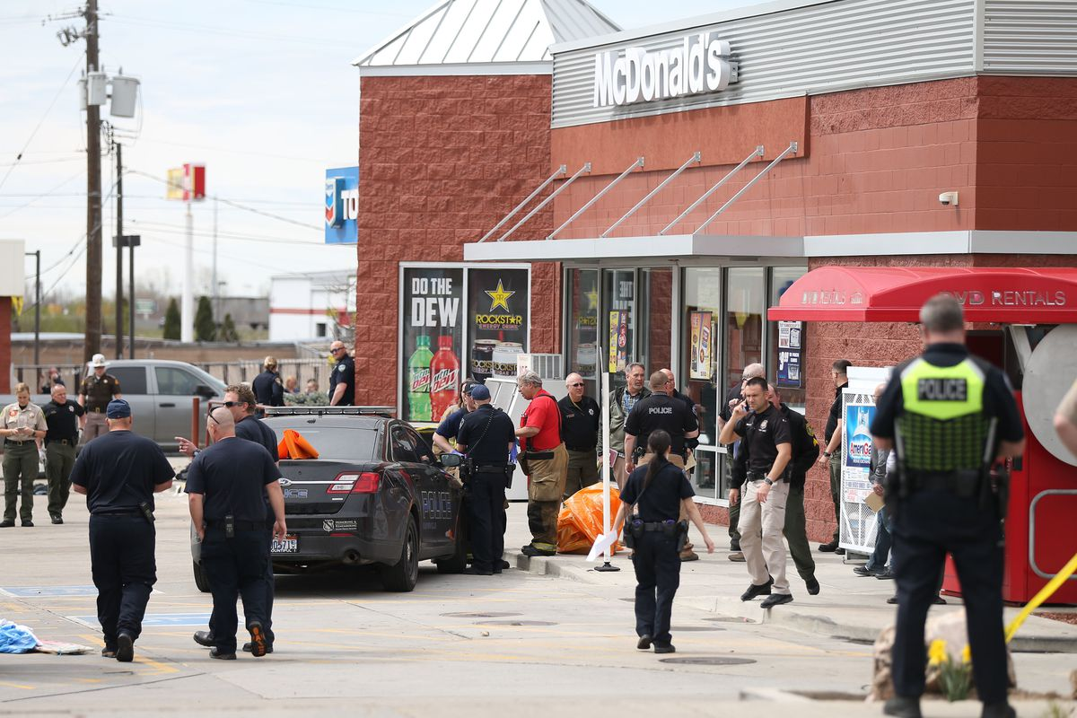 FILE - Law enforcement and fire officials convene at a scene where two officers and one suspect were injured at a Chevron Top Stop in Kaysville on Thursday, April 5, 2018.