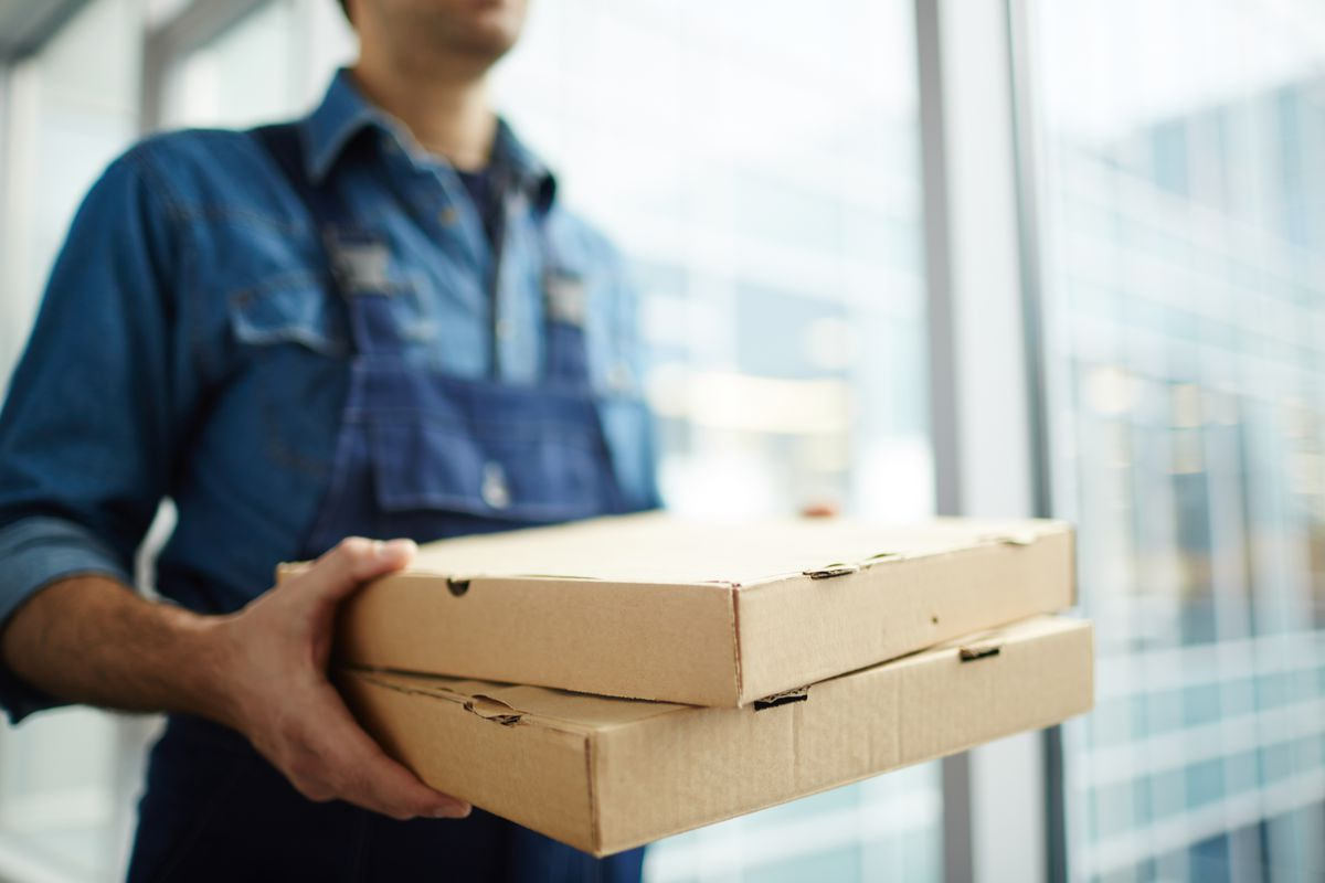 A person wearing a blue shirt and apron holding two pizza boxes
