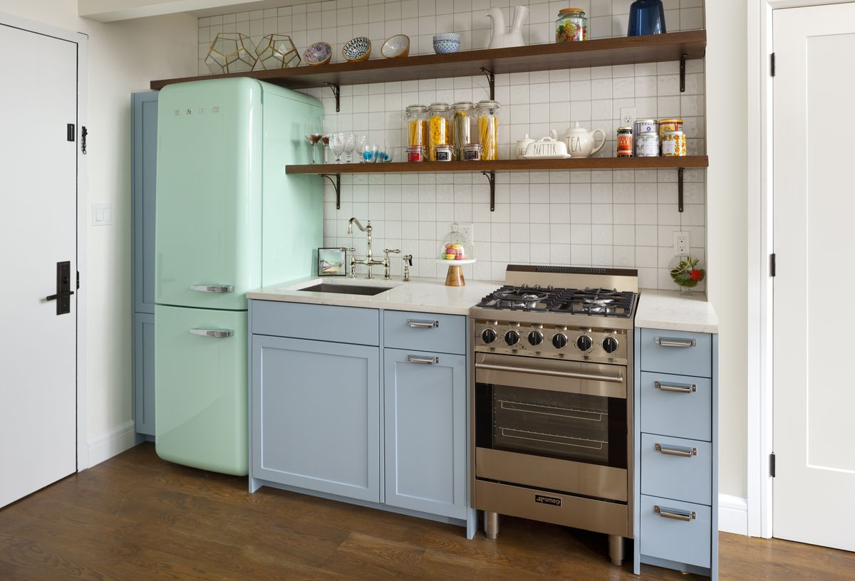 A small kitchen with a light green fridge, light blue cabinetry, and white tiles on its walls.