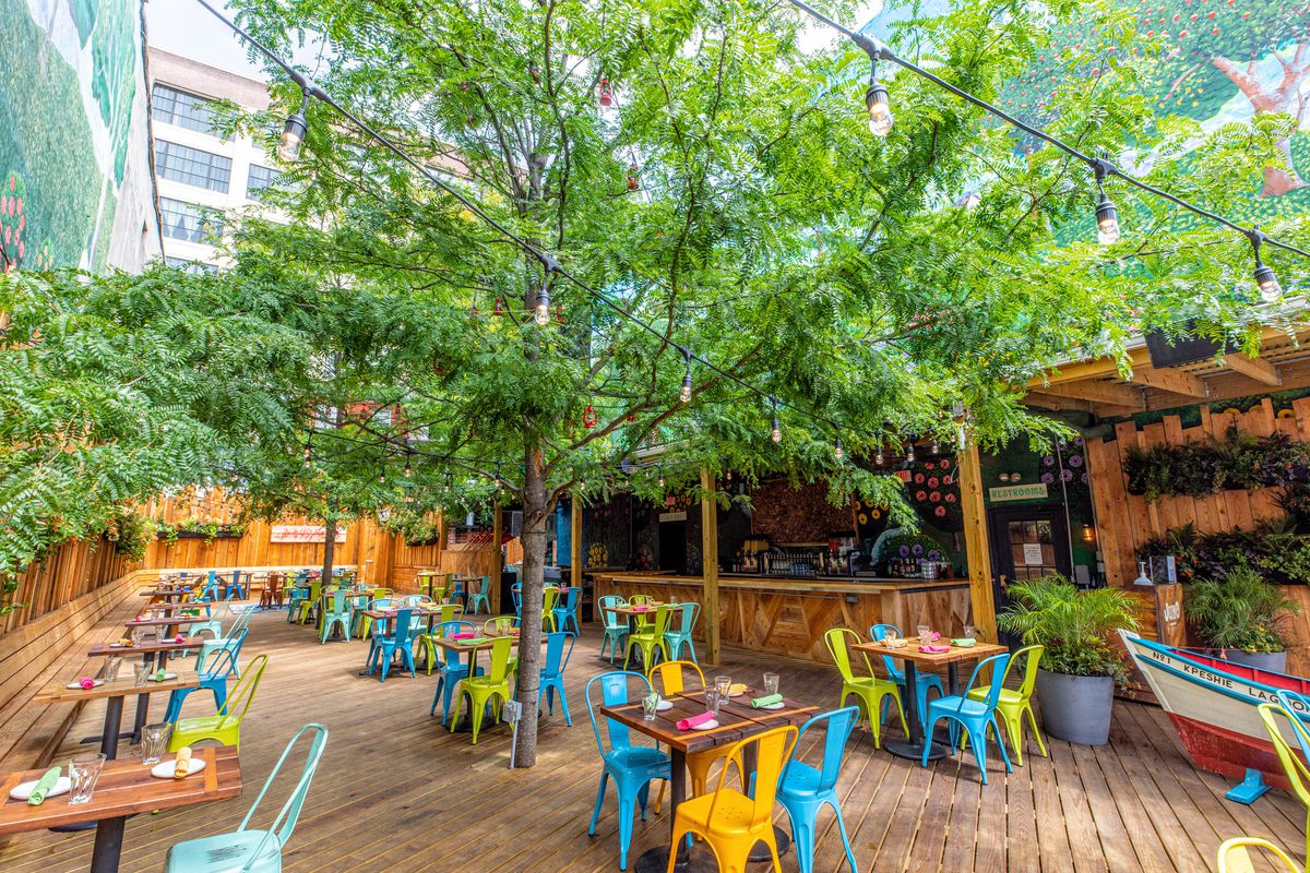 outdoor restaurant with colorful chairs and trees