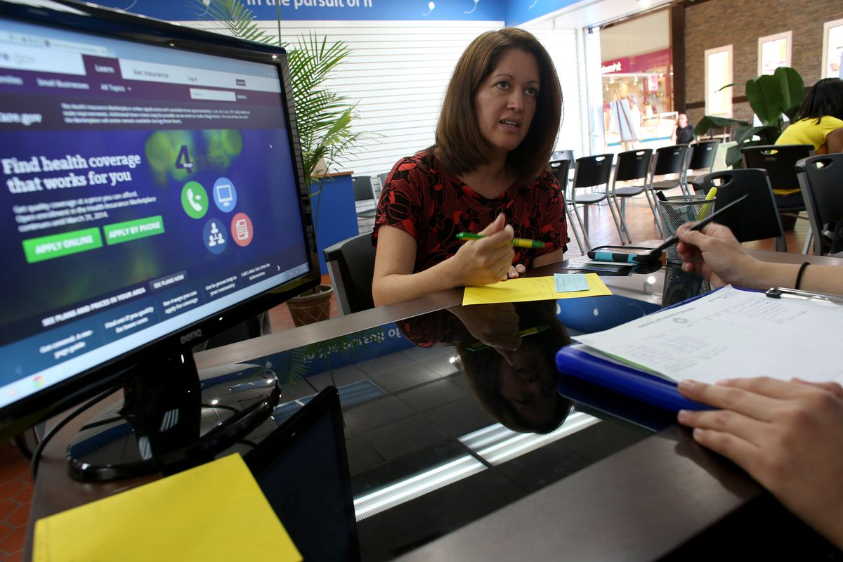Venita Mendez works with Gisselle Rubio, an insurance agent with Sunshine Life and Health Advisers, as she looks to purchase an insurance policy under the Affordable Care Act at the store setup in the Westland Mall on November 14, 2013, in Hialeah, Florida.