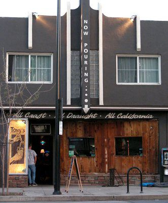 The exterior of a beer bar with dark wooden siding and a sidewalk in front.