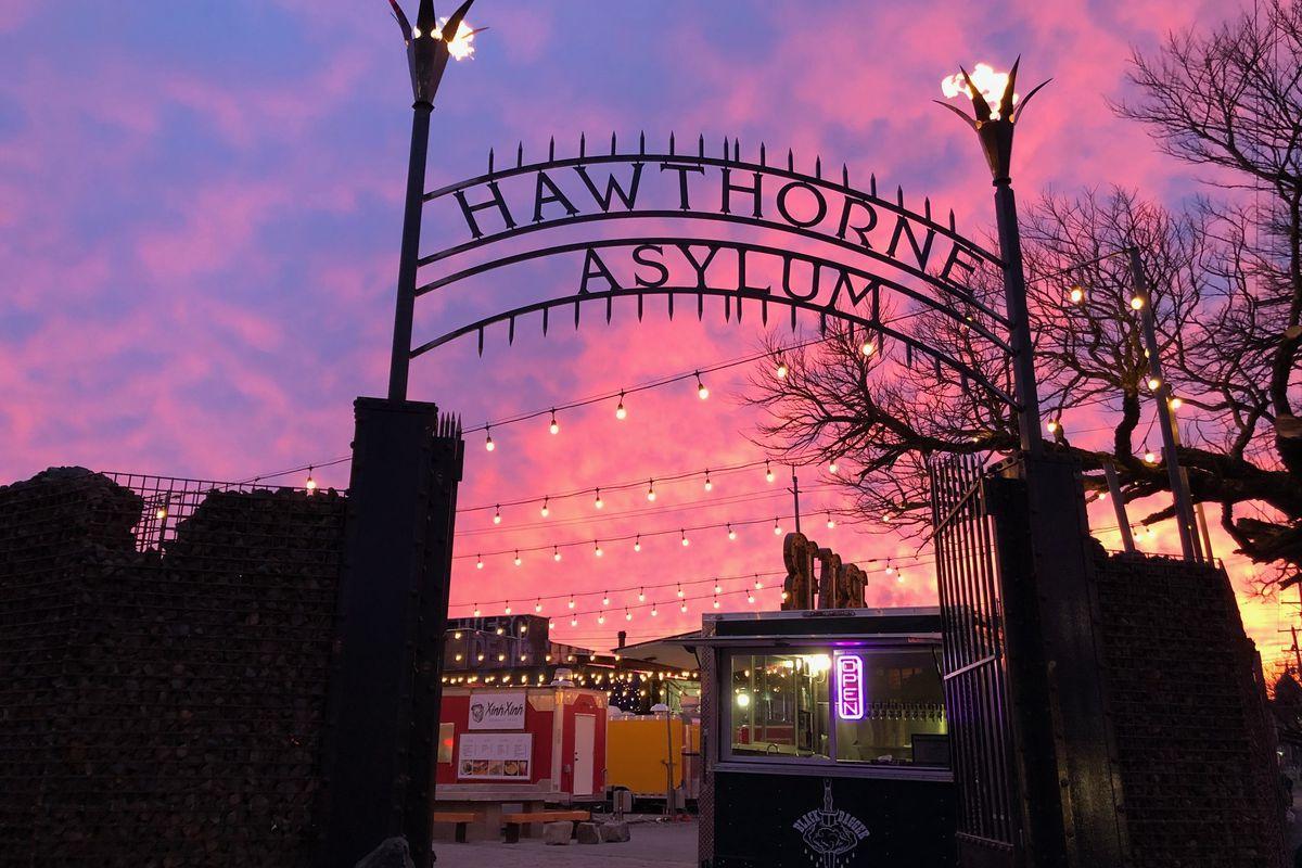 The Hawthorne Asylum food cart pod sign is dramatically lit by a vivid dusk sky.