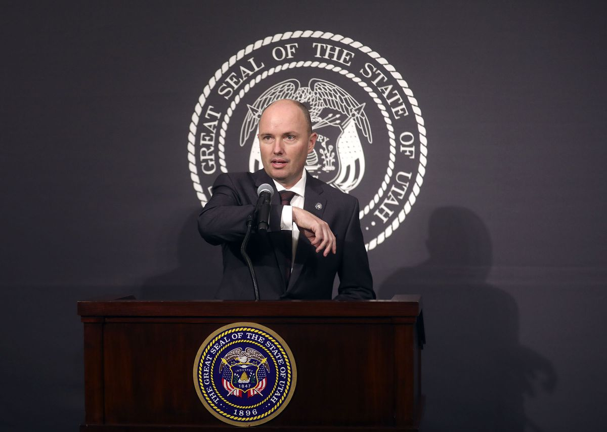 Lt. Gov. Spencer Cox uses his arm instead of his hand to raise the microphone between speakers during a daily media briefing about COVID-19 at the Capitol in Salt Lake City on Wednesday, April 1, 2020.