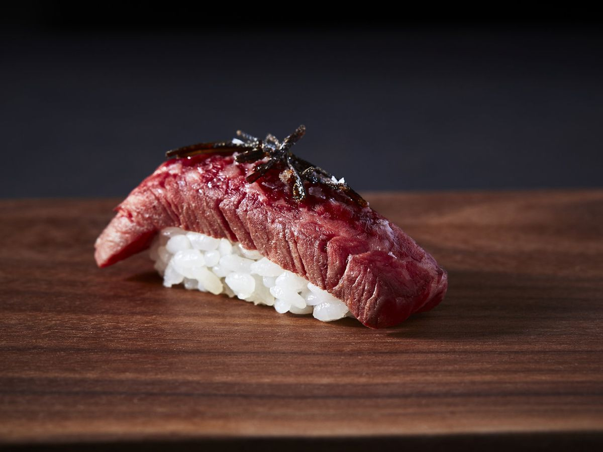 A piece of wagyu beef served on a bed of rice.
