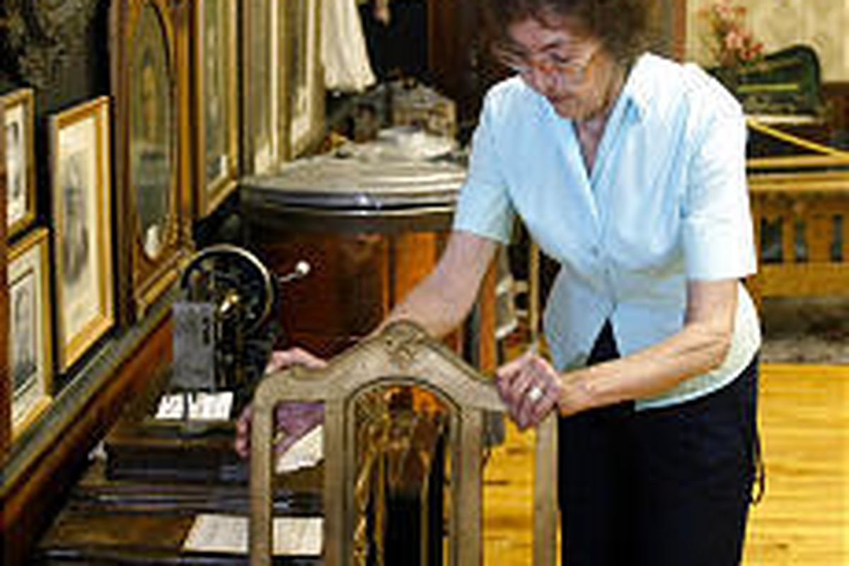 Helen Scott adjusts one of the antique chairs inside a building she loves \\\\— the Peteetneet Academy in Payson.