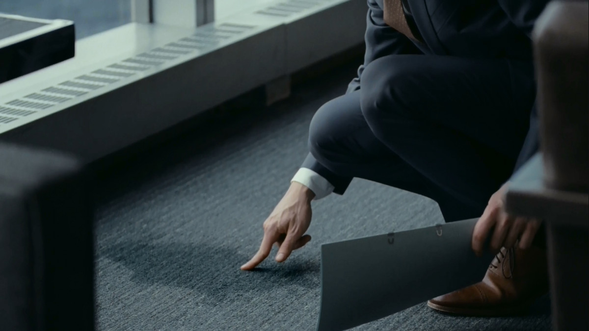A man in a suit crouched down, pointing at a pee stain on a gray carpet