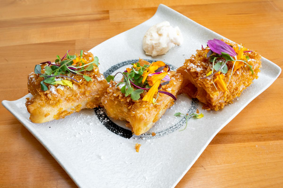 Fried shrimp toast dusted with powdered sugar and topped with microgreens and edible flowers