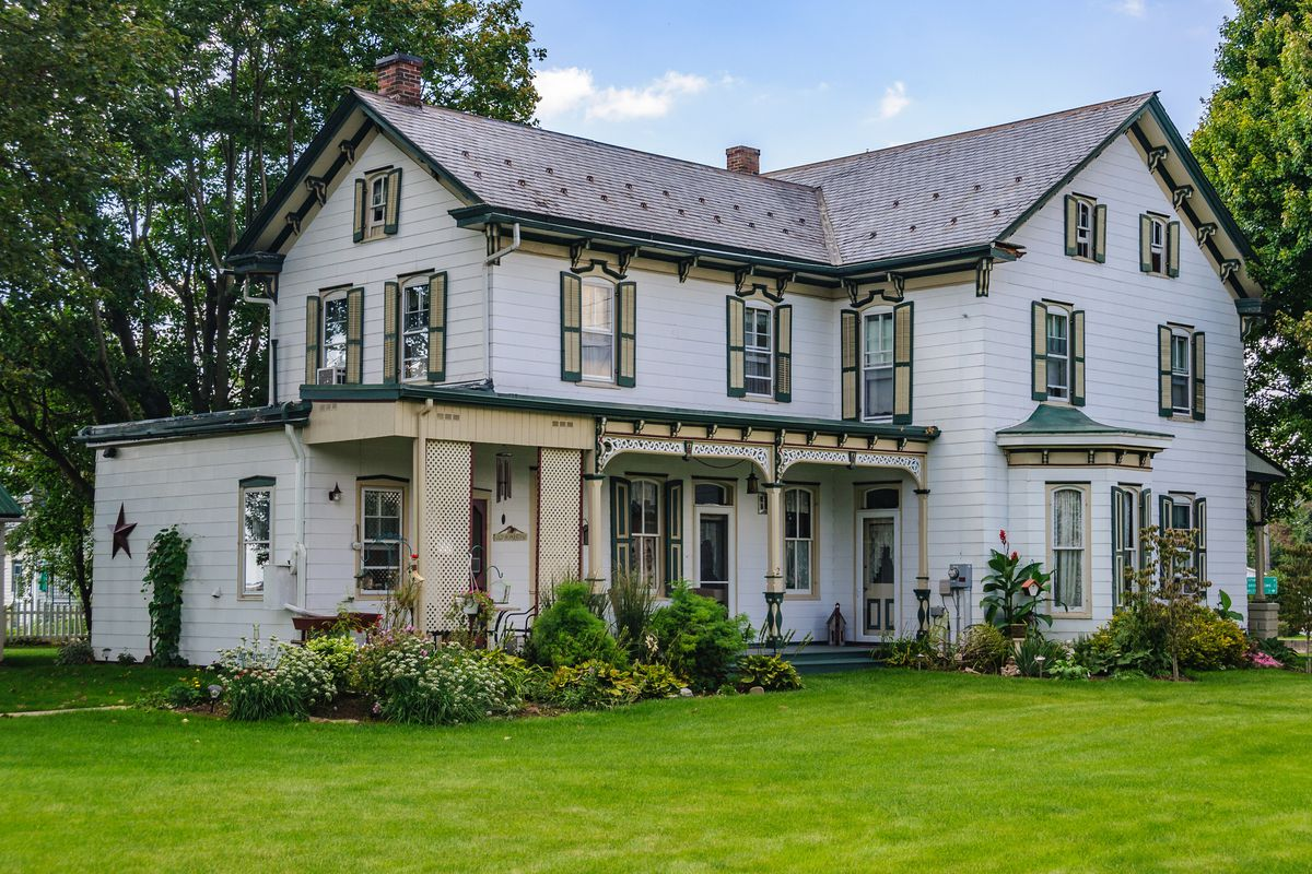 A blue-grey home in Amish, Pennsylvania with large green yard, green shrubs, and Victorian-style detailing.